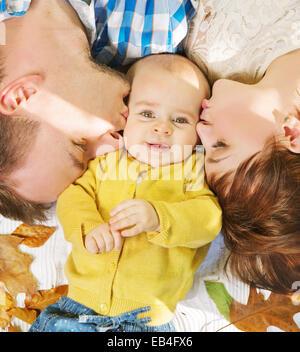 Eltern, umarmen und küssen baby - Stockfoto