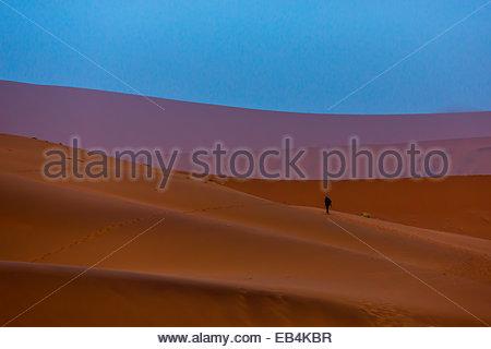 Ein Tourist auf dem Kamm einer Düne in einer Wüstenlandschaft der großen Dünen wandern. - Stockfoto