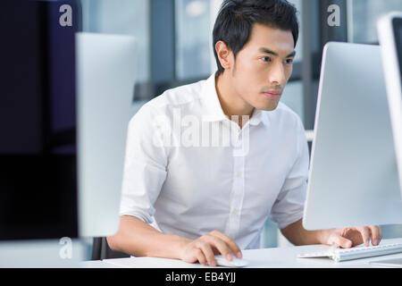 Junger Geschäftsmann mit Computer im Büro - Stockfoto