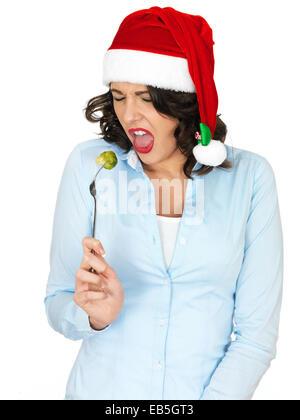 Junge Frau in Weihnachten Santa Hut Essen eine Rosenkohl - Stockfoto