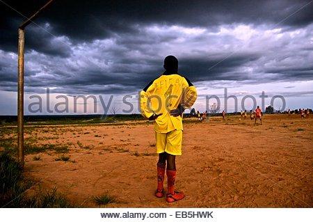 Regen Sie Wolken Webstuhl über einem Sonntag Fußballspiel in der angolanischen Stadt Cuito Cuanavale, wie ein Torwart - Stockfoto