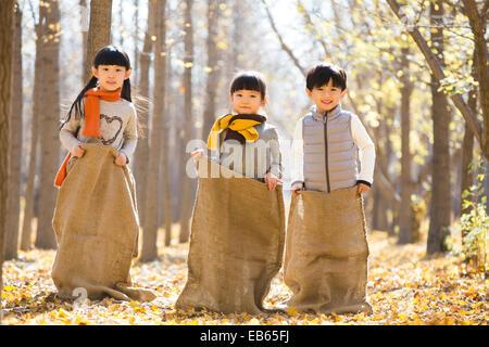 Drei Kinder mit einem Sackhüpfen im herbstlichen Wälder - Stockfoto