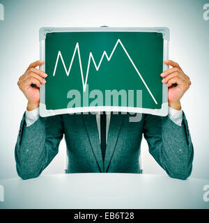 Mann trägt einen Anzug sitzen in eine Tabelle, ein Diagramm der volkswirtschaftlichen - Stockfoto