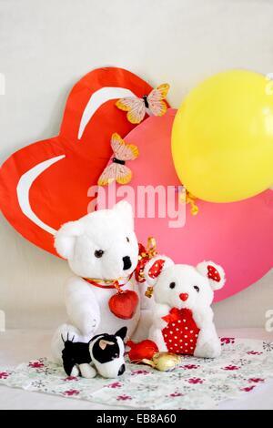 Zwei Valentine Bären sitzen auf bedruckte Serviette mit zwei Papierherzen als Kulisse ein Herz Rosa ist und die - Stockfoto