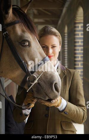 Frau im Outfit mit Pferd Reiten - Stockfoto