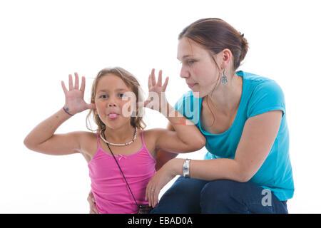 Porträt eines Mädchens ziehen ein lustiges Gesicht mit ihrer Mutter im Studio, - Stockfoto