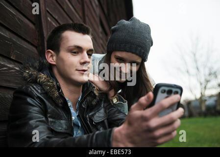 Nahaufnahme der junge Mann und junges Mädchen im freien Blick auf Handy, Deutschland - Stockfoto