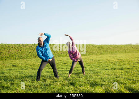 Erwachsenes paar Gymnastik im Feld, Deutschland - Stockfoto