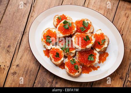 Sandwiches mit Lachs rot Kaviar und Petersilie auf weißen Teller auf hölzernen Hintergrund - Stockfoto