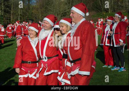 Menschen (Männer, Frauen und Kinder) Gekleidet in rot & weiß Vater Weihnachten Outfits mit Hüte & falsche Bärte, - Stockfoto