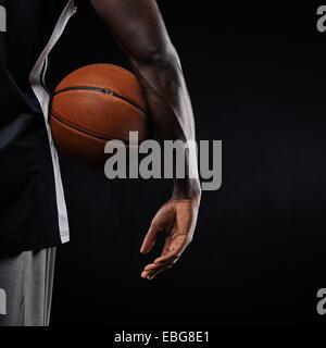 Nahaufnahme eines Basketballs in der Hand eines jungen afrikanischen Athleten vor schwarzem Hintergrund mit Textfreiraum. - Stockfoto