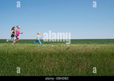 Drei Leute, die durch Feld - Stockfoto