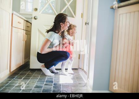 Mutter und Tochter lachend an Tür - Stockfoto