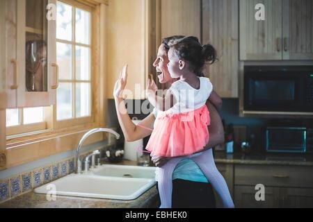Mutter und Tochter spielen in Küche Stockfoto