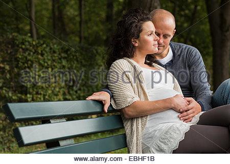 Schwangere paar streichelt Bauch auf Parkbank - Stockfoto