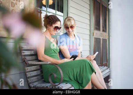 Zwei Mitte erwachsenen Frau betrachten Smartphone auf Veranda