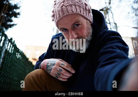 Reifer Mann mit Arm, Selbstporträt zu hocken - Stockfoto
