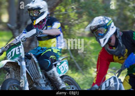 Zwei junge männliche Motocross-Fahrer Rennen durch Wald - Stockfoto