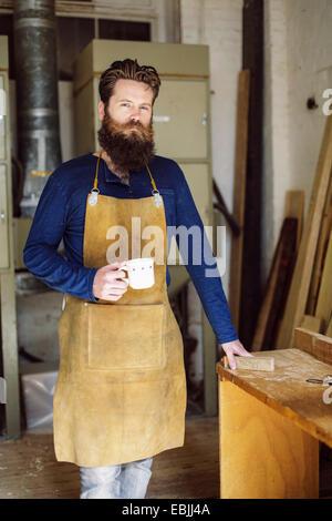 Porträt von Mitte adult Handwerker Kaffeetrinken in Orgelwerkstatt - Stockfoto