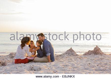 Paar mit zwei Mädchen essen Kuchen am Strand, Toskana, Italien - Stockfoto