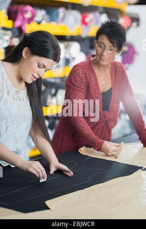 Zwei Näherinnen Kreidung Umriss auf Textil auf Arbeitstisch - Stockfoto