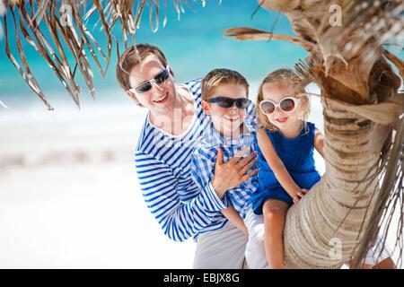 Vater und zwei Kinder sitzen am Stamm der Palme am tropischen Strand, Mexiko - Stockfoto