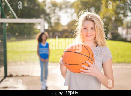 Porträt der jungen Frau hält basketball