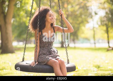 Porträt der jungen Frau auf Reifenschaukel - Stockfoto