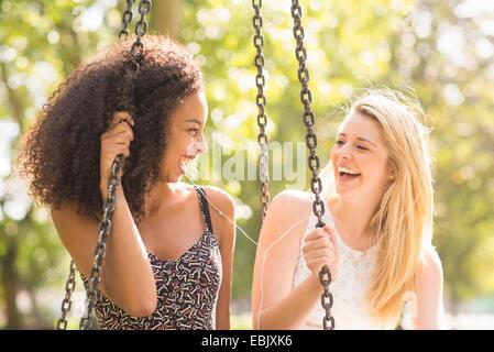 Zwei junge Frauen sitzen auf Park schwingen lachen - Stockfoto