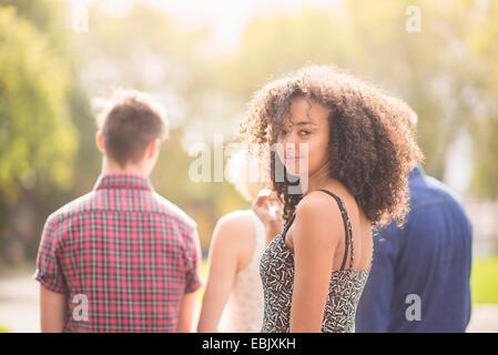 Junge Frau im Park mit Freunden über die Schulter schauen - Stockfoto