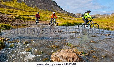 Drei Mountainbiker Radfahren durch heiße Fluss, Tal Reykjadalur, South West Island - Stockfoto