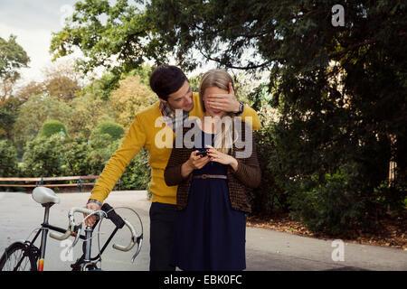 Junger Mann für Freundinnen Augen im park - Stockfoto