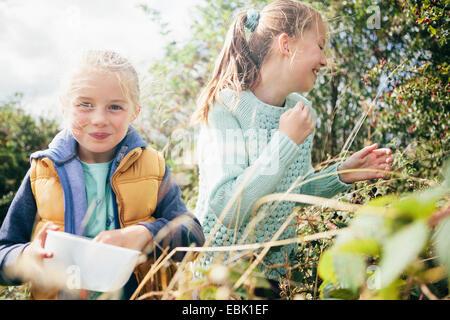 Zwei Mädchen pflücken Brombeeren - Stockfoto