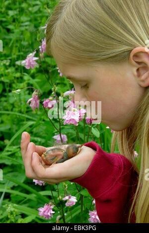 Amsel (Turdus Merula), Mädchen im Garten mit verwaisten federlose Huhn in der hand - Stockfoto
