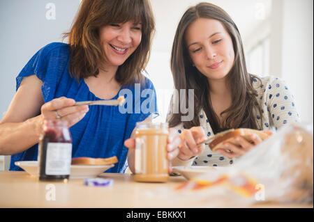 Mutter und Tochter (14-15) machen Erdnuss Butter und Gelee sandwiches - Stockfoto
