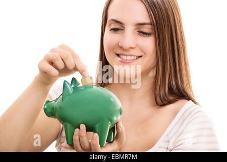 Junge Mädchen Geld in einem Sparschwein, auf weißem Hintergrund. - Stockfoto