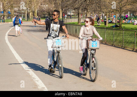 Zwei Menschen Radfahren auf Boris Leihfahrräder im Hyde Park, London, England, Großbritannien - Stockfoto