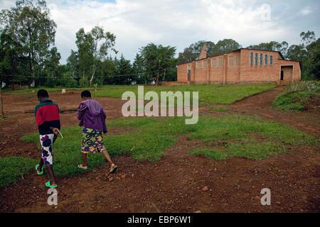 zwei Mädchen, die zu Fuß über einen Platz vor einem bescheidenen Schlamm gemauerte Kirche, Burundi, Cankuzo, in - Stockfoto