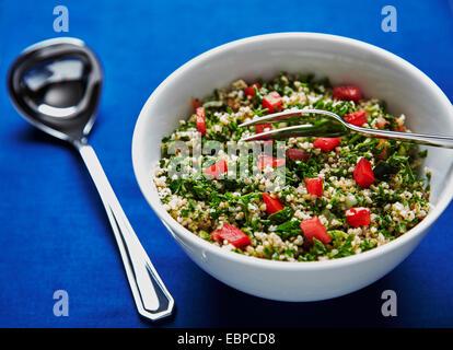 Taboulé Salat in einer weißen Schüssel auf einem dunkelblauen Hintergrund mit silbernen Löffel und einer Gabel serviert - Stockfoto