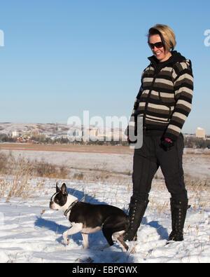 Frau, die im Stadtpark zu Fuß nach Boston Terrier geht - Stockfoto