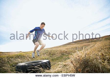 Mann springt Crossfit Reifen auf sonnigen ländlichen Gebiet - Stockfoto