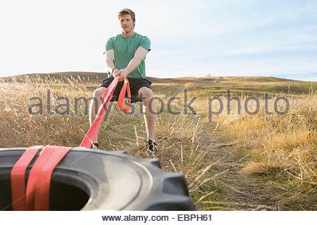 Man zieht Crossfit Reifen auf sonnigen ländlichen Gebiet - Stockfoto