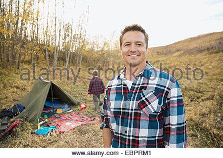 Porträt von lächelnden Mann außerhalb Zelt am Campingplatz - Stockfoto
