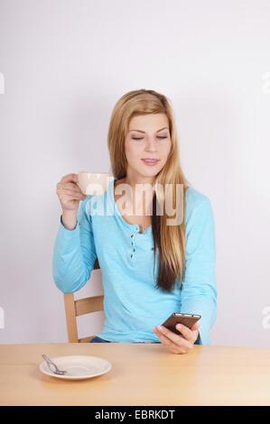 junge Frau Tasse Kaffee trinken und ihr Handy überprüfen - Stockfoto