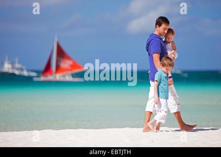 Vater mit seinen Kindern am tropischen Strand, Segelboot im Hintergrund zu Fuß - Stockfoto