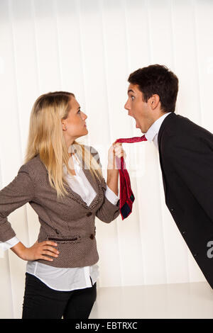 selbstbewusste Frau einen erstaunten Mann an seine Krawatte hochziehen - Stockfoto