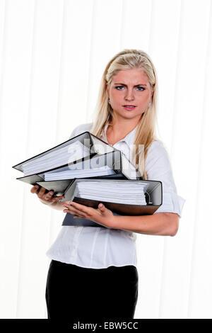 junge Frau mit Haufen Arbeit - Stockfoto