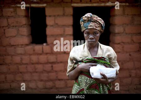 Frau in traditioneller Kleidung vor einer Schlamm-Backstein-Haus im Bau, Burundi, Karuzi, Buhiga - Stockfoto