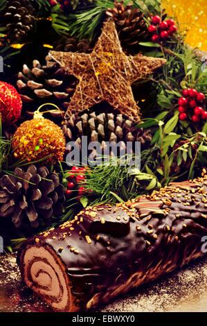 Nahaufnahme eines Kuchens Yule Log, traditionelle Weihnachten Zeit, auf einem Tisch verziert mit Weihnachtskugeln - Stockfoto