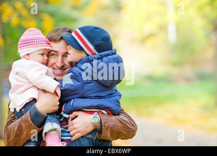 Junger Vater mit zwei Kindern genießen wunderschönen Herbsttag - Stockfoto